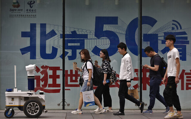 Illustrative: A police robot mounted with surveillance cameras watches people walking past a 5G network advertisement in a shopping district in Beijing, Wednesday, May 15, 2019. (AP/Andy Wong)