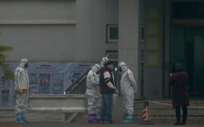 Staff in biohazard suits hold a metal stretcher by the in-patient department of Wuhan Medical Treatment Center, where some infected with a novel coronavirus are being treated, in Wuhan, China, Tuesday, Jan. 21, 2020. (AP Photo/Dake Kang)
