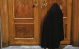 A woman prays behind a closed door of Masoume shrine in the city of Qom, some 80 miles (125 kilometers) south of the capital Tehran, Iran, March 16, 2020 (AP Photo/Str)