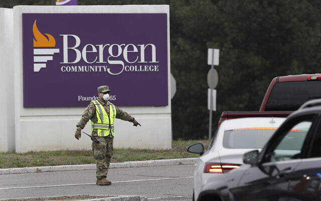 A member of the New Jersey National Guard directs traffic at the entrance to a drive-thru COVID-19 testing center in Paramus, N.J., Friday, March 20, 2020. The facility opened Friday in Bergen County which has been the state's hardest-hit area.  (AP Photo/Seth Wenig)