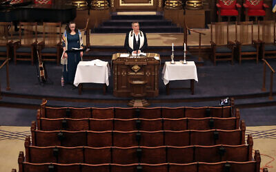 Illustrative: Rodef Shalom Rabbi Aaron Bisno, center, delivers his sermon with soloist Molly May, left, during an Erev Shabbat service that is being streamed live on Facebook, Friday, March 20, 2020.(AP Photo/Gene J. Puskar)