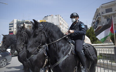 Horse-mounted Palestinian Authority policemen deploy to enforce measures against the coronavirus, in the West Bank city of Ramallah, March 23, 2020. (AP Photo/Nasser Nasser)