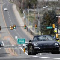 A motorist guides his Porsche convertible along a nearly-empty South University Boulevard, April 5, 2020, in Cherry Hills Village, Colo. (AP Photo/David Zalubowski)