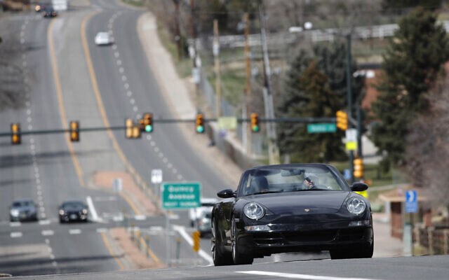 A motorist guides his Porsche convertible along a nearly-empty South University Boulevard, April 5, 2020, in Cherry Hills Village, Colo. (AP Photo/David Zalubowski)
