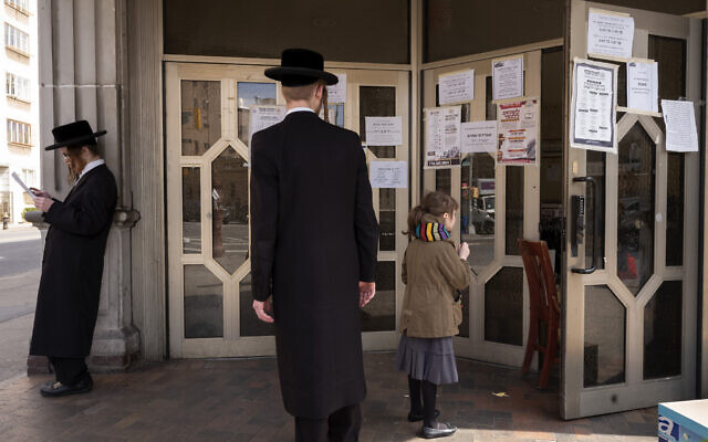 A man stops to read an announcement at Congregation Divrei Yoel in the Williamsburg neighborhood of Brooklyn, Tuesday, April 7, 2020 in New York. The synagogue is closed to gatherings due to the coronavirus. (AP/Mark Lennihan)