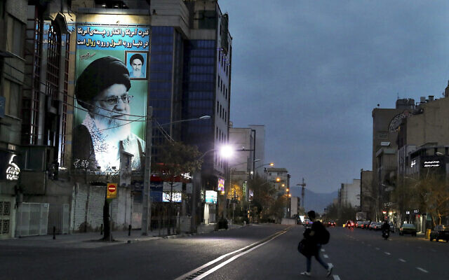 In this Tuesday, March 24, 2020 photo, a pedestrian crosses an empty street with a portrait of Iran's Supreme Leader Ayatollah Ali Khamenei, in Tehran, Iran. (AP/Ebrahim Noroozi)