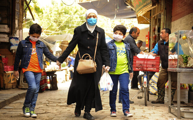 In this photo released on April 18, 2020, a Syrian woman walks with her sons wearing masks due to the coronavirus, in Damascus, Syria. (SANA via AP)
