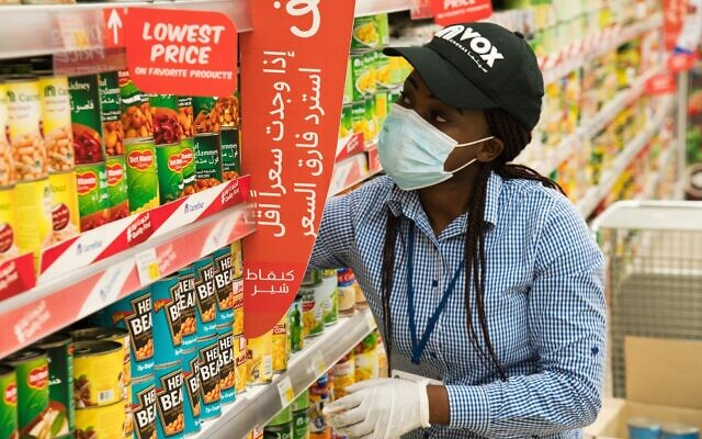 In this April 19, 2020 photo, Vox Cinema employee Jackline Nansamba of Uganda stocks shelves at a Carrefour supermarket while wearing a face mask amid the coronavirus pandemic in Dubai, United Arab Emirates. (AP Photo/Jon Gambrell)