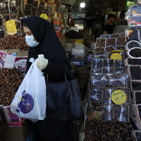 A woman wearing a protective face mask and gloves to help prevent the spread of the coronavirus carries her purchases as she leaves a store which sells dates, a favorite fruit for the Muslim holy fasting month of Ramadan, in Tehran on April 27, 2020. (AP Photo/Vahid Salemi)