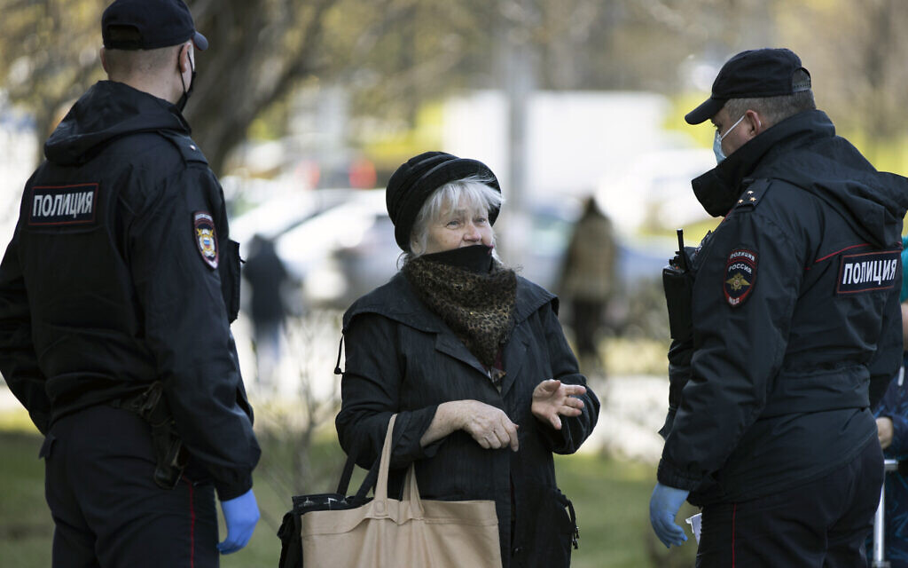Russian police officers, wearing face masks to protect from coronavirus, speak to a woman as they check her documents to ensure a self-isolation regime due to coronavirus, in Moscow, Russia, April 28, 2020. (AP Photo/Alexander Zemlianichenko)
