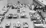 """In this 1918 photo, volunteer nurses from the American Red Cross tend to influenza patients in the Oakland Municipal Auditorium, used as a temporary hospital. (Edward A. """"Doc"""" Rogers/Library of Congress via AP)"""
