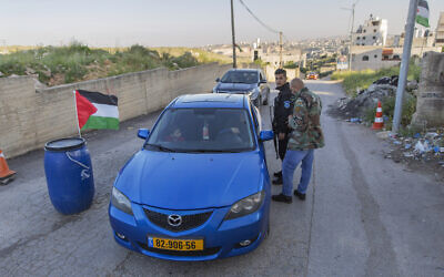 In this April 28, 2020 photo, Palestinian security forces stop vehicles, part of lockdown and quarantine measures to protect residents, at a checkpoint on an entrance to the West Bank village of Kafr Aqab, near Ramallah. (AP Photo/Nasser Nasser)
