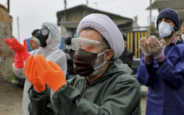 Mourners wearing protective clothing, face masks and gloves, pray over the body of a victim who died after being infected with the new coronavirus, in the outskirts of the Iranian city of Babol on April 30, 2020. (AP Photo/Ebrahim Noroozi)