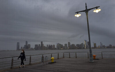 A woman wears a face mask as she walks on Pier 45 in Hudson River Park, April 30, 2020, in New York (AP Photo/Mark Lennihan)