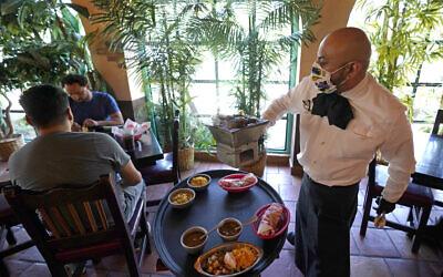 Waiter Marcos Huerta, right, serves a grill of fajitas at El Tiempo Cantina May 1, 2020, in Houston (AP Photo/David J. Phillip)
