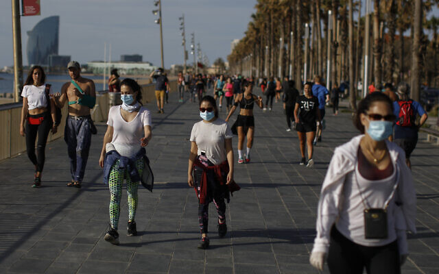 People walk along a seafront promenade in Barcelona, Spain, May 2, 2020 (AP Photo/Emilio Morenatti)