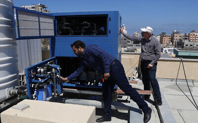 In this April 30, 2020, photo, Palestinian engineer Raed Nakhal from Palestine Children Relief Fund, right, and engineer Abdullah Dewik, check the GEN-M machine that generates safe drinking water from air at the roof of al-Rantisi pediatric hospital in Gaza City. (AP Photo/Adel Hana)