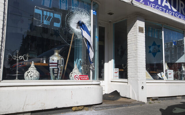 Broken glass and a stone lie on the pavement as an Israeli flag sticks out of the window of HaCarmel kosher restaurant in Amsterdam, Netherlands, May 8, 2020, after a man smashed the window (AP Photo/Peter Dejong)