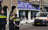An Israeli flag sticks out of the window of HaCarmel kosher restaurant in Amsterdam, Netherlands, May 8, 2020, after a man smashed the window. (AP Photo/Peter Dejong)