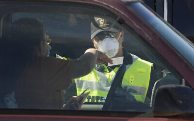 A New Mexico state police officer screens cars for compliance with an emergency lockdown order that bans nonessential visitors and limits vehicle passengers to two people as they enter Gallup, New Mexico, May 7, 2020 (AP Photo/Morgan Lee)