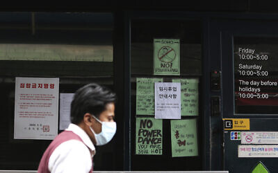 A man wearing a face mask passes by the entrance of a temporarily closed dance club in Seoul, South Korea, May 10, 2020 (AP Photo/Ahn Young-joon)