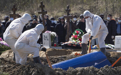 Gravediggers wearing protective suits bury a COVID-19 victim as relatives and friends stand at a safe distance, in the coronavirus section of a cemetery in Kolpino, outside St. Petersburg, Russia, May 10, 2020. (AP/Dmitri Lovetsky)