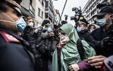 Silvia Romano, escorted by Carabinieri officers, arrives at her home wearing the green hijab typical of Somali Muslim women and a surgical mask to guard against COVID-19, in Milan, Italy, May 11, 2020. (AP Photo/Luca Bruno, File )