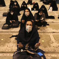 Worshipers wearing protective face masks to help prevent the spread of the coronavirus pray at the mosque of the Tehran University in Laylat al-Qadr, or the night of destiny, during holy fasting month of Ramadan, Iran, May 12, 2020. (Vahid Salemi/AP)