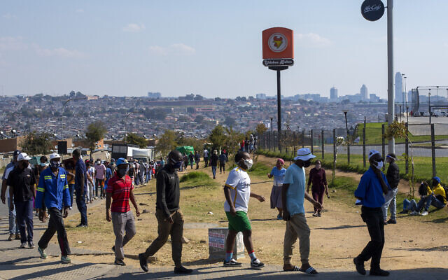 People wearing face masks to protect against coronavirus, queue to walk through a disinfecting spray booths aimed to combat the spread of COVID-19, before doing shopping at Alexandra township in Johannesburg, South Africa, Wednesday, May 13, 2020. (AP Photo/Themba Hadebe)