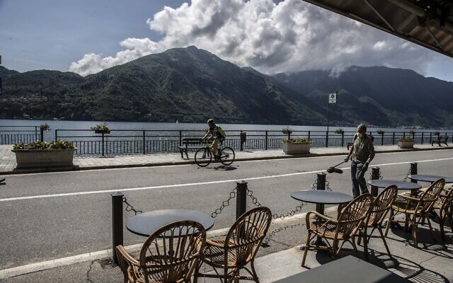 A worker walks holding a lawn mower as a biker rides past a cafe outdoor tables in Tremezzo, Lake Como, Italy, May 14, 2020 (AP Photo/Luca Bruno)