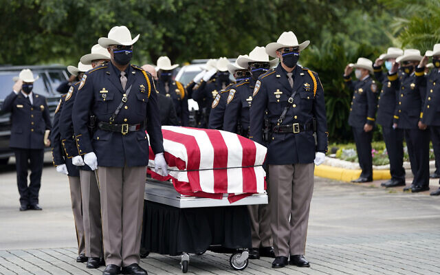 Members of the Harris County Sheriff's Honor Guard move the casket of Sgt. Raymond Scholwinski, who died after contracting COVID-19, during a funeral service, May 14, 2020, in Humble, Texas. (AP Photo/David J. Phillip)