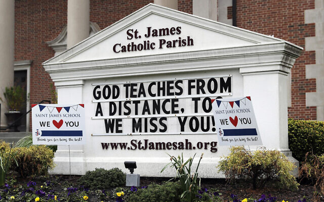 A sign shows at St. James Catholic Parish during the coronavirus pandemic in Arlington Heights, Ill., Thursday, May 14, 2020. The Archdiocese of Chicago, as well as other Catholic dioceses throughout the state announced phased plans to begin reopening Catholic churches, starting in Chicago with small gatherings for baptisms, weddings, funerals and confession as early as May 23. (AP Photo/Nam Y. Huh)
