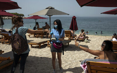 Swimmers pay for sunbeds with an employee of a beach bar who wears a protective mask against coronavirus, at Alimos beach, near Athens, on Saturday, May 16, 2020 (AP Photo/Yorgos Karahalis)