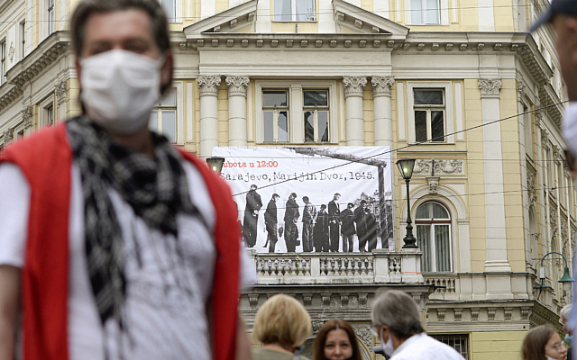 People walk backdropped by a banner showing victims executed by hanging in 1945 by the pro-Nazi Croatian WWII Ustasha regime in Sarajevo, Bosnia, on May 16, 2020. (AP/Kemal Softic)