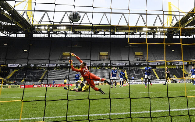 Dortmund's Raphael Guerreiro scores his side's 4th goal against Schalke's goalkeeper Markus Schubert during the German Bundesliga soccer match between Borussia Dortmund and Schalke 04 in Dortmund, Germany, Saturday, May 16, 2020. (AP/Martin Meissner, Pool)
