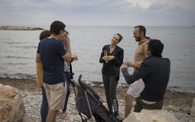 A group of friends celebrate a birthday with champagne at a beach in Marseille, southern France, May 16, 2020 (AP Photo/Daniel Cole)