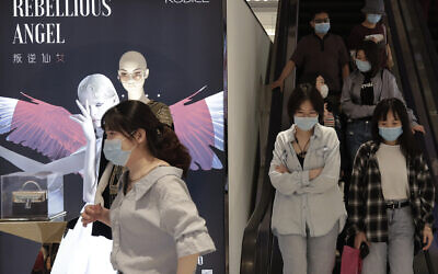 People wearing protective face masks to help curb the spread of the new coronavirus ride an escalator at a shopping mall in Beijing, May 17, 2020. (Andy Wong/AP)