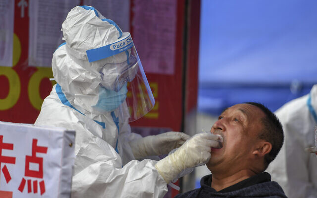 In this May 17, 2020, photo released by Xinhua News Agency, a medical worker collects sample for COVID-19 testing at the Tongji community in Shulan in northeastern China's Jilin Province. Authorities have tightened restrictions in parts of Jilin province in response to a local cluster. (Zhang Nan/Xinhua via AP)