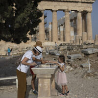 Visitors wash their hands in front of ancient Parthenon temple at the Acropolis hill of Athens, on May 18, 2020 (AP Photo/Petros Giannakouris)