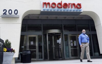 A man stands outside an entrance to a Moderna, Inc., building, Monday, May 18, 2020, in Cambridge, Mass. Moderna announced Monday that an experimental vaccine against the coronavirus showed encouraging results in very early testing, triggering hoped-for immune responses in eight healthy, middle-aged volunteers.(AP Photo/Bill Sikes)