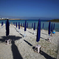"In this photo taken on Sunday, May 10, 2020, people walk among folded beach umbrellas dotted on an empty stretch of ""Nissi beach"" in Ayia Napa, Cyprus, a seaside resort that's popular with tourists from Europe and beyond. (AP Photo/Petros Karadjias)"