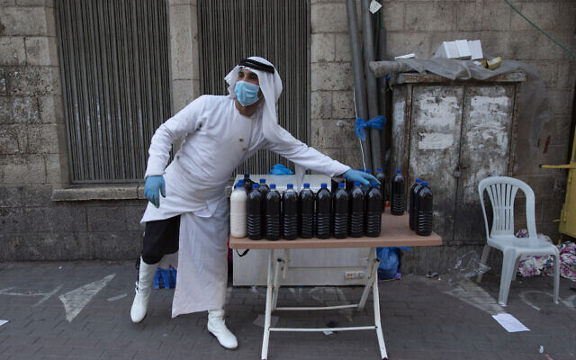 A Palestinian vendor with a mask displays his fresh fruit juice in the street as the markets remain partly closed, part of a lockdown and quarantine measures to protect residents from the coronavirus, in the West Bank city of Ramallah, May 19, 2020. (Nasser Nasser/AP)