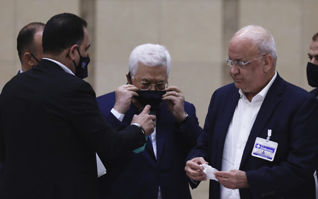 Palestinian Authority President Mahmoud Abbas puts on a face mask as he heads a leadership meeting at his headquarters in the West Bank city of Ramallah on May 19, 2020. (Alaa Badarneh/Pool Photo via AP)