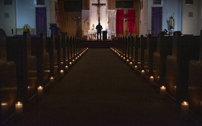ILLUSTRATIVE - In this April 11, 2020, file photo, a person films Easter Vigil Mass at St. Patrick Church in North Hollywood, California (AP Photo/Damian Dovarganes)