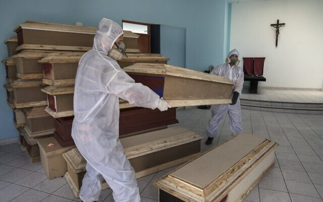 Funeral home workers prepare to load coffins into a waiting vehicle to transport to a public hospital in order to pick up bodies of deceased persons who are suspected to have died from the new coronavirus, at a crematorium in Lima, Peru. (AP Photo/Rodrigo Abd)