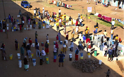 In this April, 24, 2020, photo, people wait to fetch water from a row of communal taps that the group Doctors Without Borders provided in a suburb of Harare, Zimbabwe  (AP Photo/Tsvangirayi Mukwazhi)