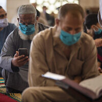 Palestinians wearing face masks read the Quran as they attend the last Friday noon Prayer of the holy month of Ramadan, in a mosque in Gaza City,  May. 22, 2020.  (AP Photo/Khalil Hamra)