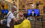 A barber wearing a mask to help stop the spread of the new coronavirus listens to a speech by Hezbollah leader Hassan Nasrallah being broadcast on Hezbollah's al-Manar TV channel, to mark Al-Quds (Jerusalem) day while he cuts a customer's hair at his salon, in the southern suburb of Beirut, Lebanon, Friday, May 22, 2020. (AP Photo/Hassan Ammar)