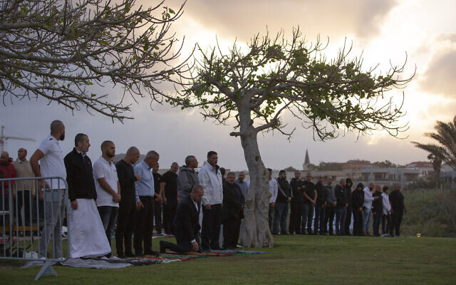 Muslim worshipers offer Eid al-Fitr prayer that marks the end of the holy fasting month of Ramadan at a park in Jaffa, May 24, 2020. (AP Photo/Oded Balilty)