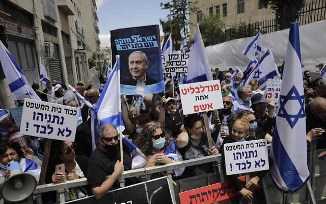 Right wing activists hold flags and signs in support of Prime Minister Benjamin Netanyahu during a demonstration outside the Jerusalem District Court, May 24, 2020 (AP Photo/Sebastian Scheiner)